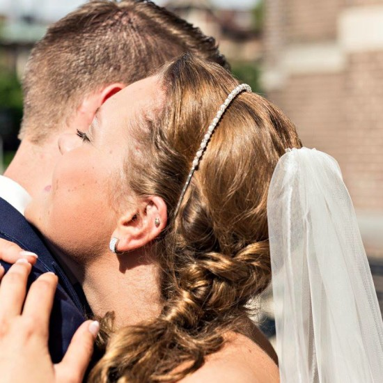 Bruidspaar geeft elkaar een knuffel. Foto Bobby Regensburg