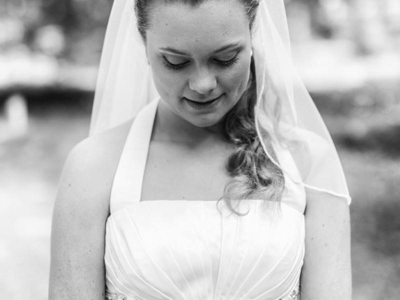 Bruid kijkt naar beneden. Foto is in zwart-wit. Foto Bobby Regensburg