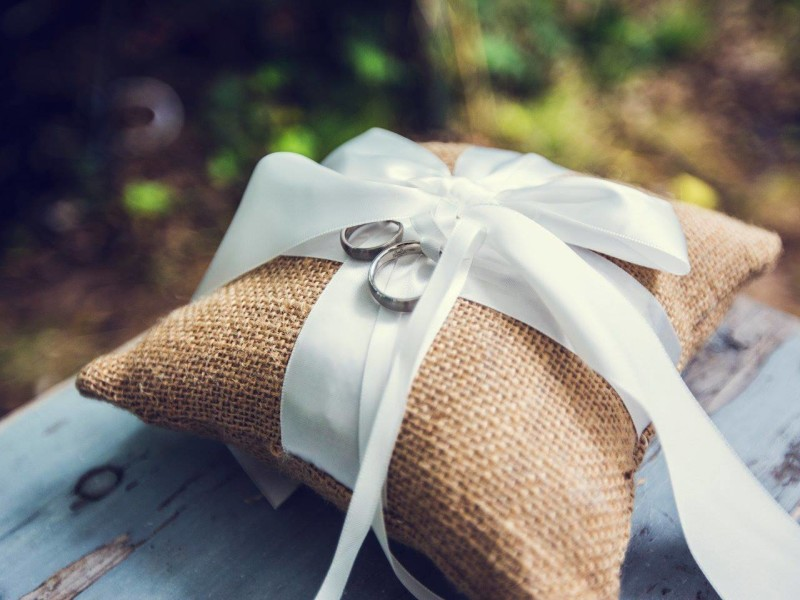 Trouwringen op een jute kussentje met wit lint. Foto Bobby Regensburg