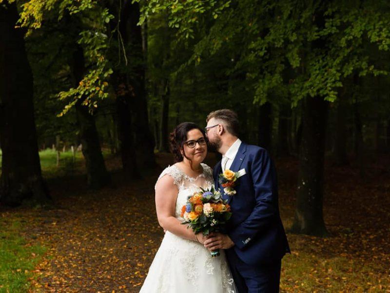 Bruidegom fluistert iets in oor bruid