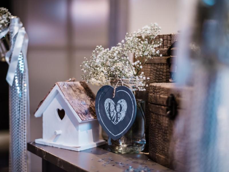 Wit vogelhuisje. Love bordje aan vaasje met witte bloemetjes. Foto Tovergoud
