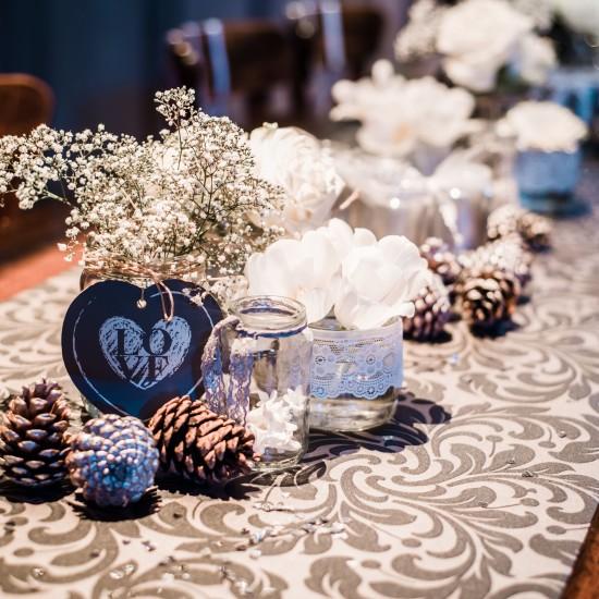 Dennenappels op een tafel. Daarachter een vaasje met love bordje met witte bloemetjes. Daarnaast glazen potjes met kant erom heen. Foto Tovergoud