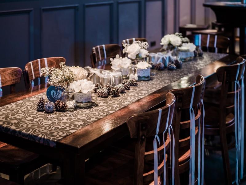 Versierde tafel met dennenappels en vaasjes met witte bloemen. Foto Tovergoud