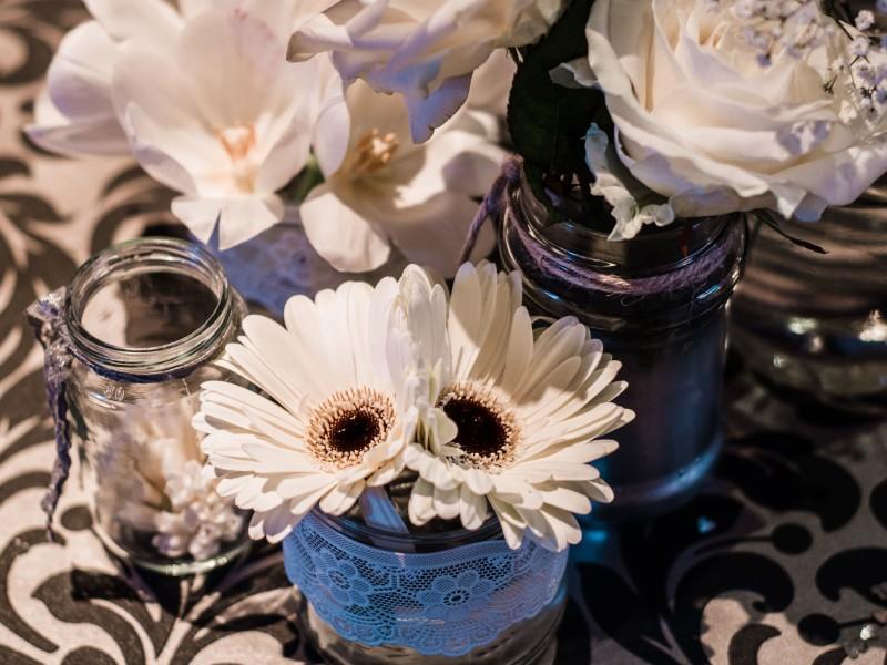 Witte bloemen in glazen vaasjes. Foto Tovergoud