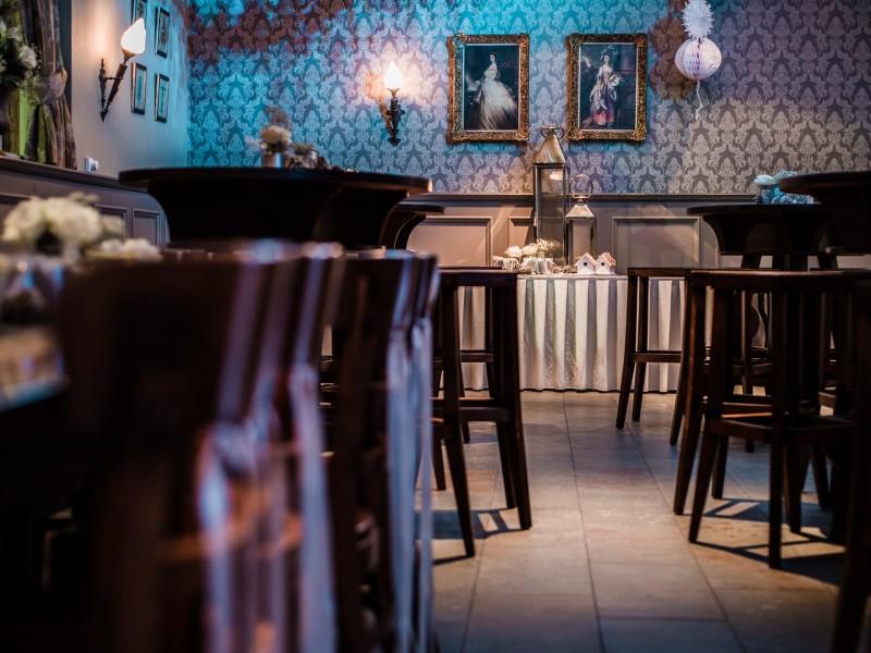 Doorkijk op bruinen stoelen en barkrukken naar een gedecoreerde tafel. Foto Tovergoud