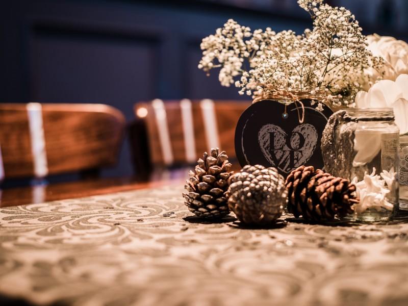 Dennenappels op een tafel met daarachter vaasjes met bloemen. Foto Tovergoud