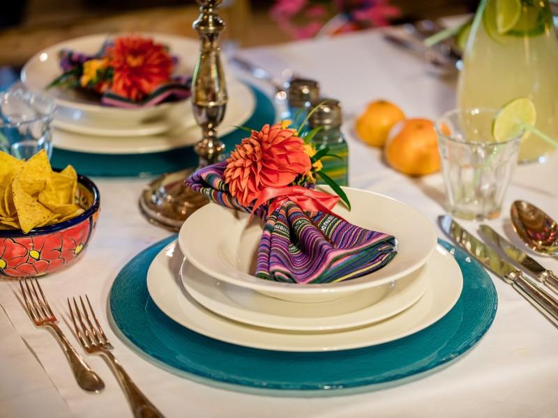 Deel van een gedekte tafel. Kleurig servet op borden. Daarnaast een bakje met Nachos. Foto Eppel Fotografie