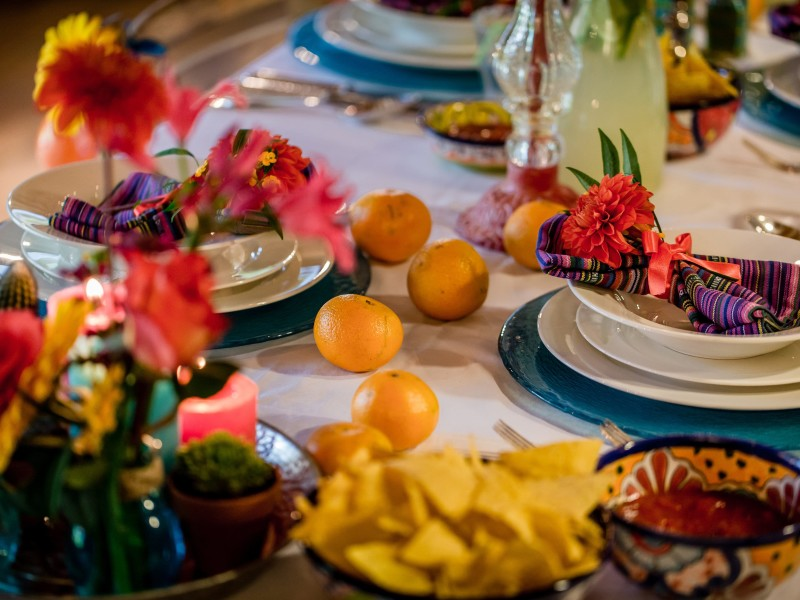 Deel van een gedekte tafel met veel kleuren en mandarijnen. Foto Eppel Fotografie