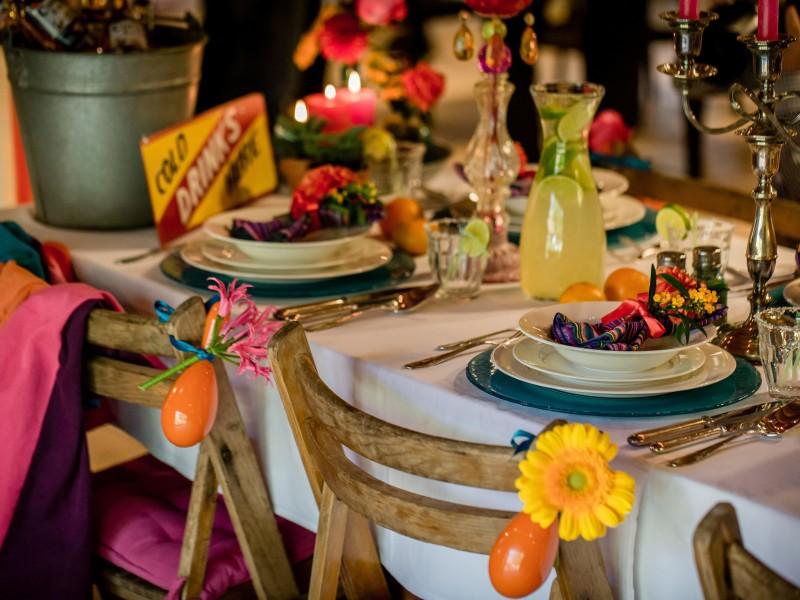 Deel van een gedekte tafel met houten stoelen met bloemen eraan. Foto Eppel Fotografie