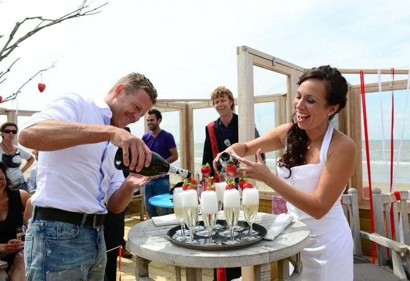 Bruidspaar schenkt de champagne in. Foto Liselotte Schoo