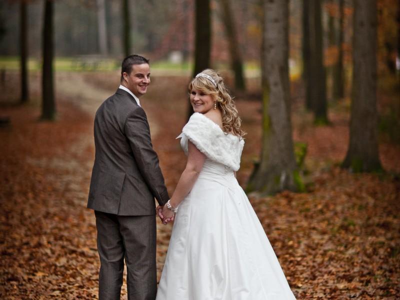 Bruidspaar vanaf de achterkant kijkend naar de fotograaf in het bos. Foto FotoMX