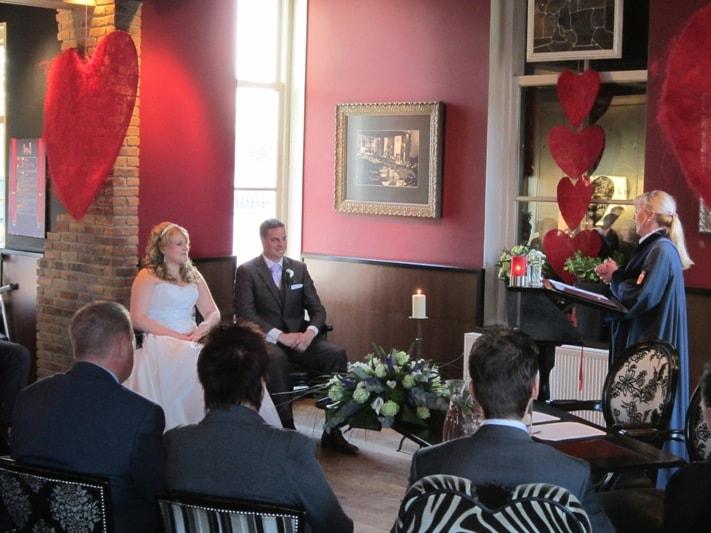 Bruidspaar zit naast elkaar tijdens de ceremonie. Rechts staat de ambtenaar. Foto FotoMX