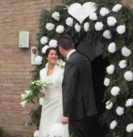 Bruidspaar voor een haag van dennentakken met witte bloemen. Foto Geoman