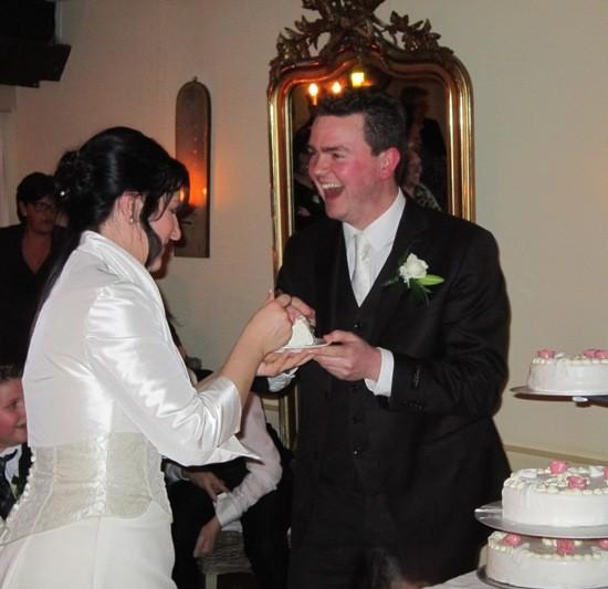 Bruidspaar met een schoteltje met een stuk taart. Foto Geoman