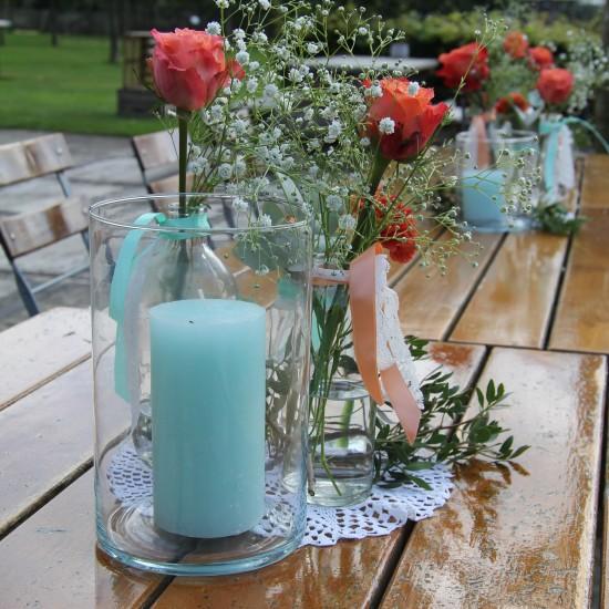 Glazen kaarsenhouder met lichtblauwe kaars. Daarachter een vaasje met lint eromheen met bloemen.