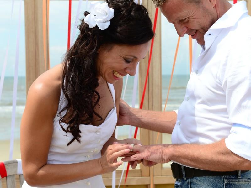 Bruid schuift ring om bruidegom zijn vinger. Foto Liselotte Schoo