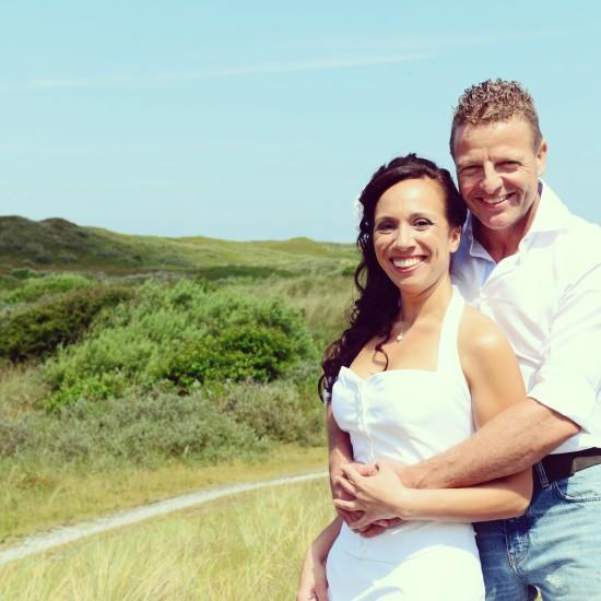 Bruidegom staat achter Bruid en houd haar vast. Achtergrond zijn de groene duinen te zien. Foto Liselotte Schoo
