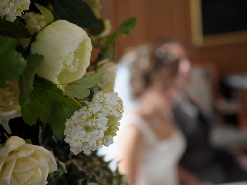 Closeup van een wit boeket. Op de achtergrond is vaag het bruidspaar te zien. Foto Ton Otten