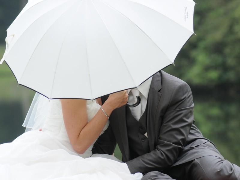 Bruidspaar met een witte paraplu voor het gezicht. Foto Ton Otten