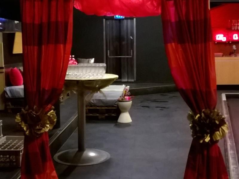 Zaal Bollywood feest. Achter staat een tafel met champagne glazen.