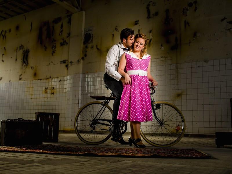 Man op een fiets staat liefdevol achter een vrouw met een roze stippel jurk. Foto Karin Keesmaat