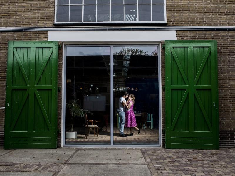 Bruidspaar dansend in een gebouw. Te zien door een groot raam met groene deuren. Foto Karin Keesmaat