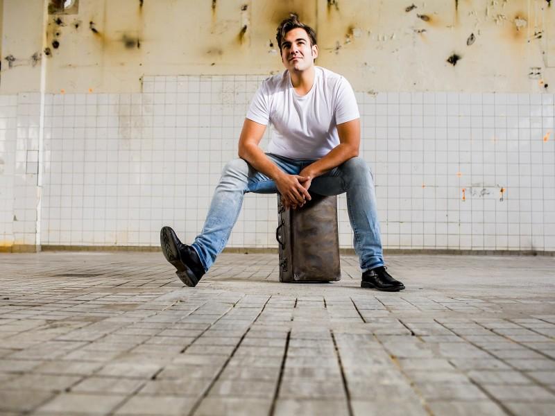 Man zit op een oude leren koffer. Foto Karin Keesmaat