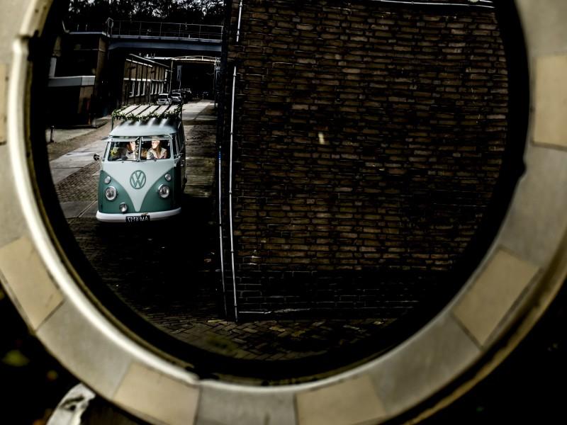 Door een rond doorkijkje een oud VW busje met het bruidspaar. Foto Karin Keesmaat