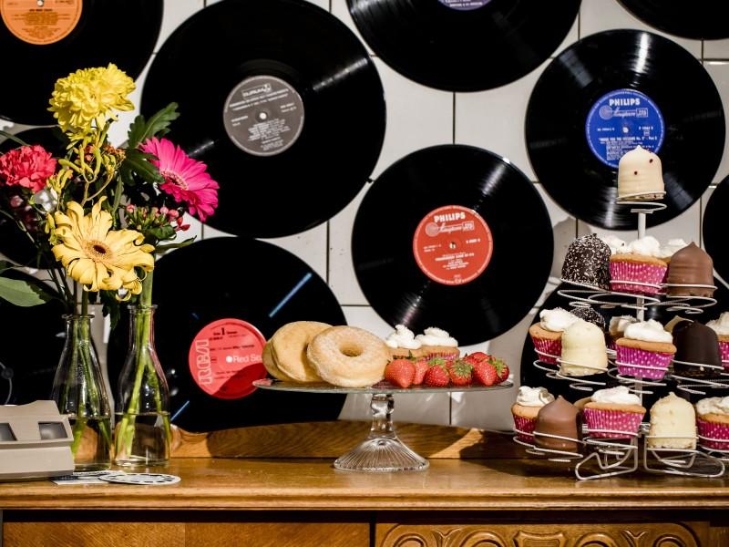 Gestylede tafel met cupcakes en donuts. Met op de muur vinylplaten. Foto Karin Keesmaat