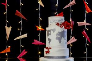 Bruidstaart met de wereld erop en vliegtuigjes erachter. Gestylde afterweddingshoot Wendy en Bradley: fotograaf Karin Keesmaat van Kijk-Kunst bruidsfotografie