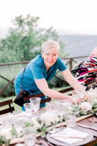 Ceremoniemeester is bezig met het bloemwerk op tafel. Foto: Jessica Photography