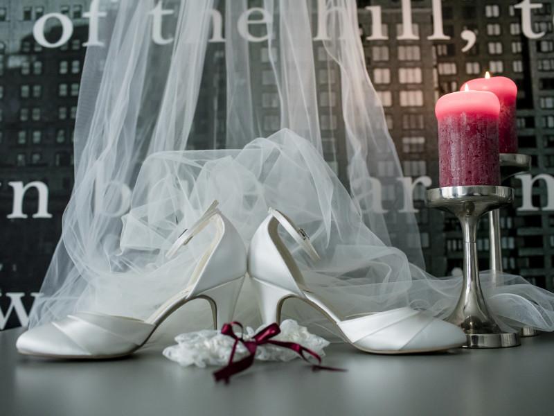 Bruidsschoenen op tafel met de sluier en 2 rode/roze kaarsen. Foto Karin Keesmaat