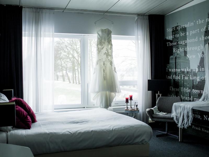 Hotel kamer met de bruidsjurk die voor het raam hangt. Foto Karin Keesmaat