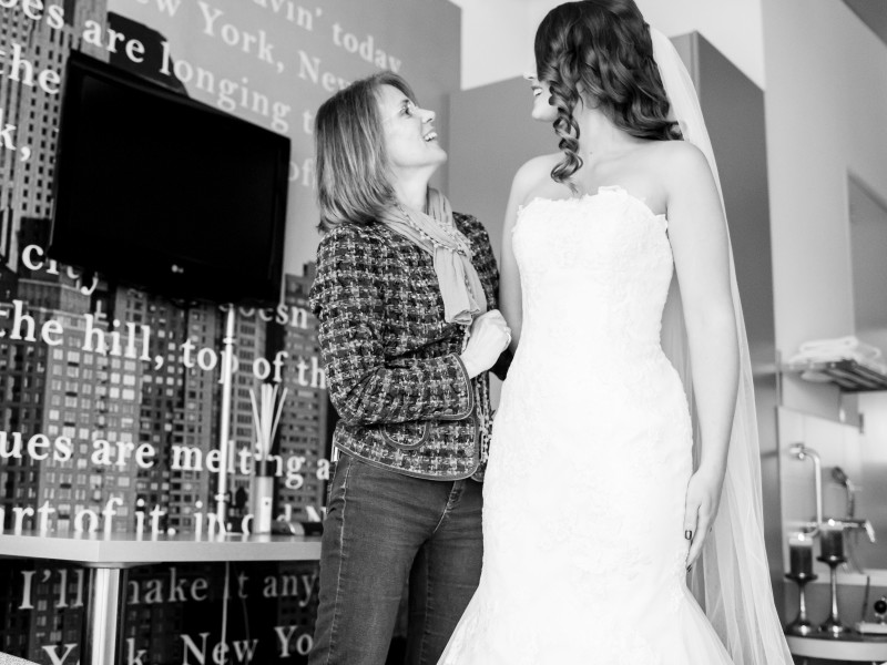 Bruid met een vrouw lachend in de hotelkamer. Foto Karin Keesmaat