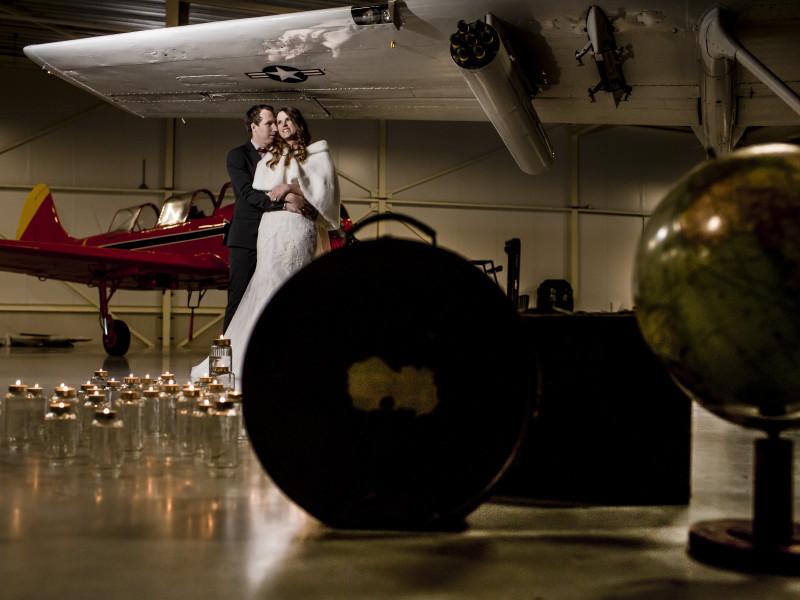 Bruidspaar met een klein rood vliegtuigje op de achtergrond. Foto Karin Keesmaat