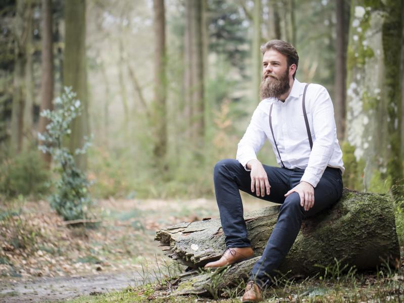 Man zit op een stuk boom in het bos. Foto Karin Keesmaat