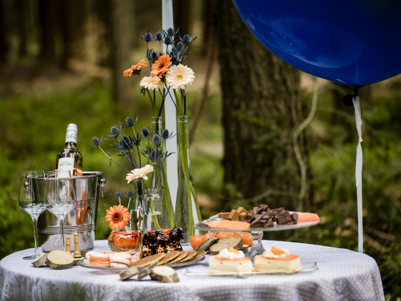 Gestylde tafel in het bos met veel oranje kleuren. Foto Karin Keesmaat