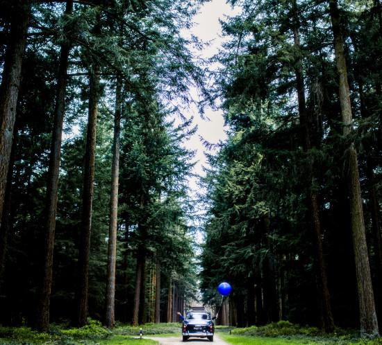 Koppel in een bos. Met grote blauwe ballonnen. Foto Karin Keesmaat