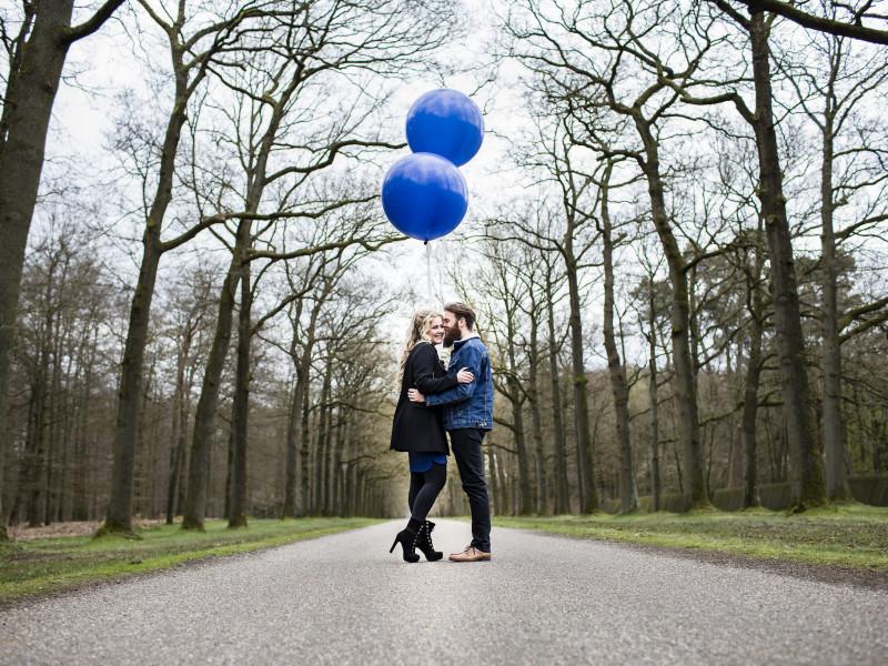 Koppel midden op de weg in een bos. Met grote blauwe ballonnen. Foto Karin Keesmaat