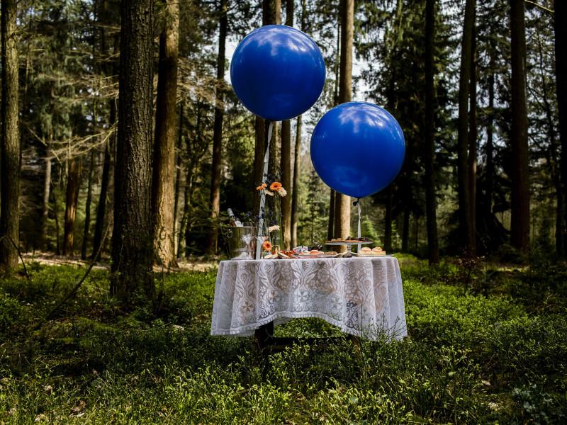 Gestylde tafel in het bos. Wit kanten tafellaken. Grote blauwe ballonnen hangen boven de tafel. Foto Karin Keesmaat