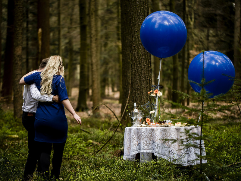 Koppel in het bos met een gedekt tafeltje met grote blauwe ballonnen. Foto Karin Keesmaat