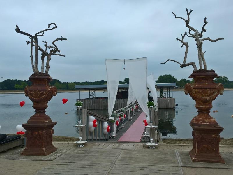 Steiger aan het water gestyled met witte en rode ballonnen.