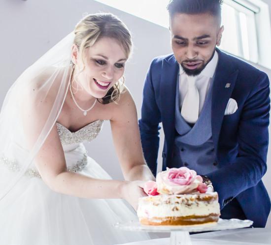 Bruid en bruidegom snijden taart aan