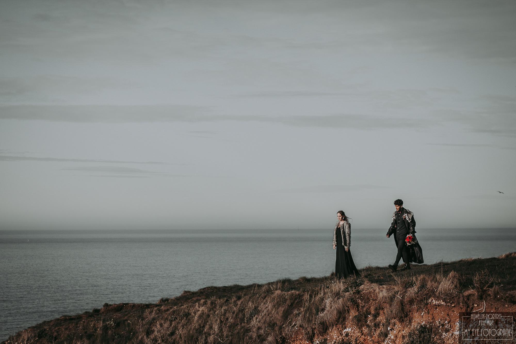 Bruidegom loopt naar bruid op klif. Foto My Eye Fotografie