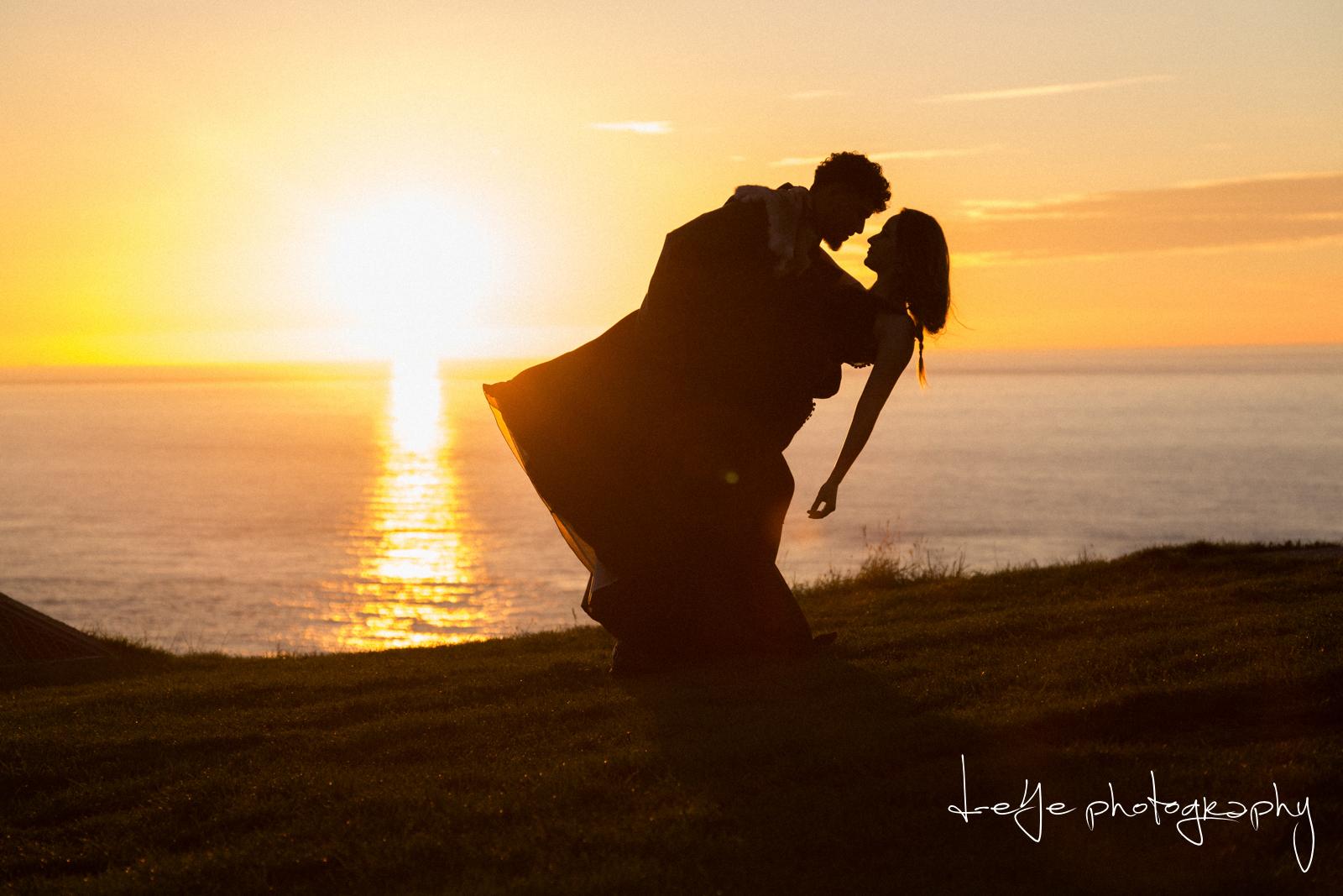 Bruidspaar bij ondergaande zon op klif. Foto D eYe Photography
