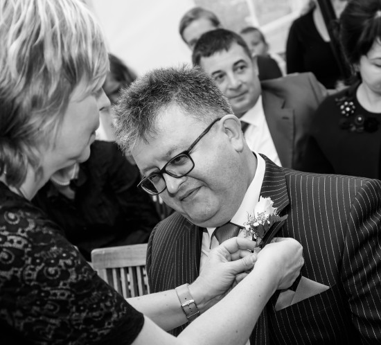 Bruiloft ceremoniemeester doet corsage op.