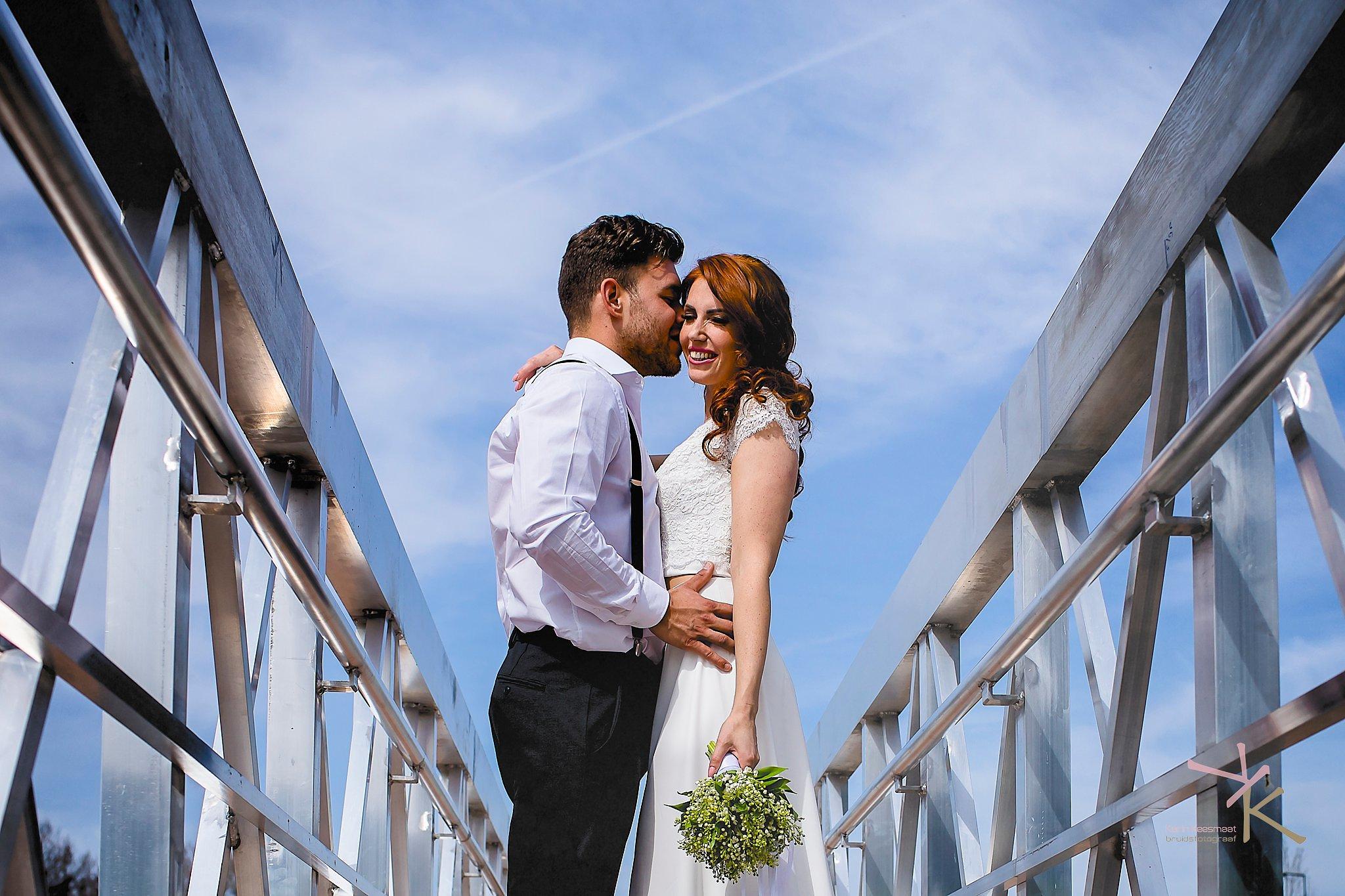 Bruidegom fluistert iets in het oor van de bruid: foto gemaakt door Karian Keesmaat van Kijk-Kunstfotografie