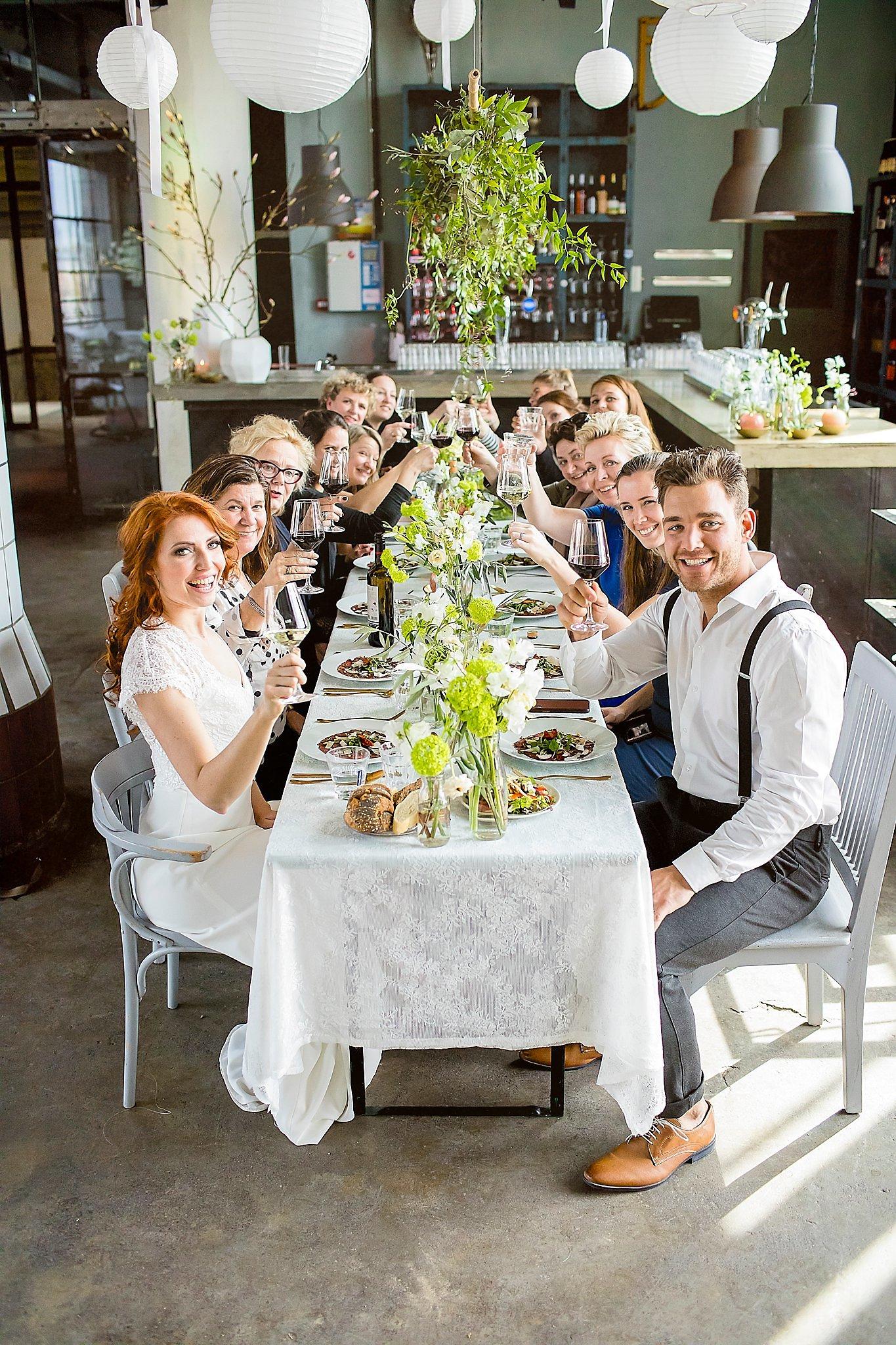 Bruidspaar met hun gasten aan tafel foto gemaakt door Karian Keesmaat van Kijk-Kunstfotografie