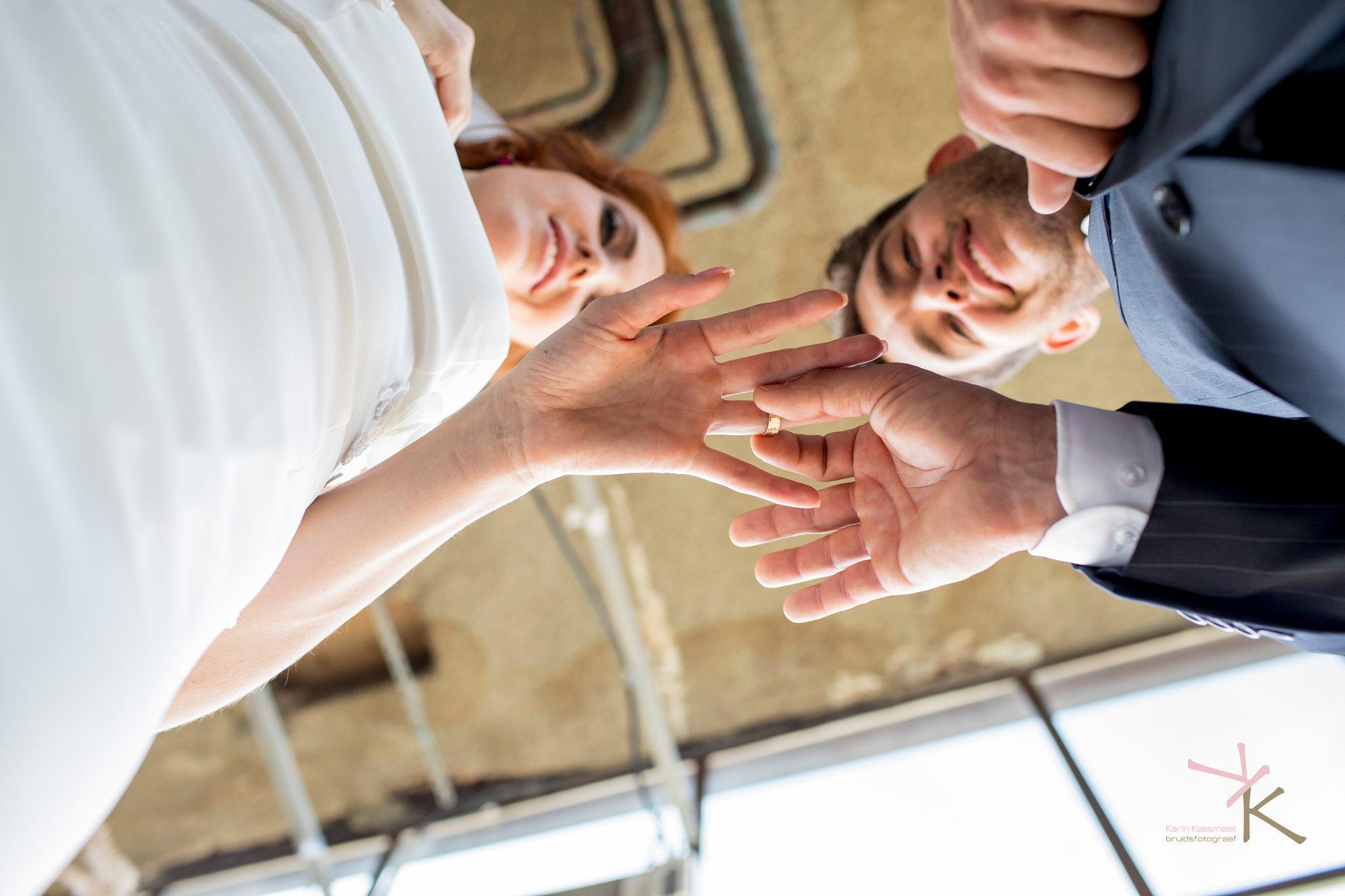 Bruid en bruidegom kijken hoe hij de ring omschuift.