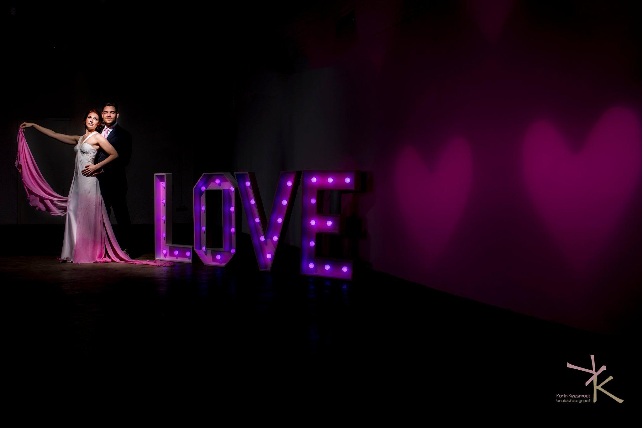 Bruidspaar bij LOVE lichtletters foto gemaakt door Karian Keesmaat van Kijk-Kunstfotografie